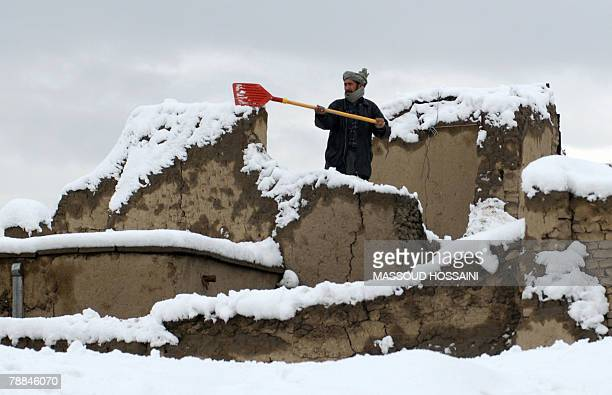 An Afghan man clears the snow from the roof of his house in Kabul 08 January 2008 At least 19 people were killed 16 were missing and scores of others...