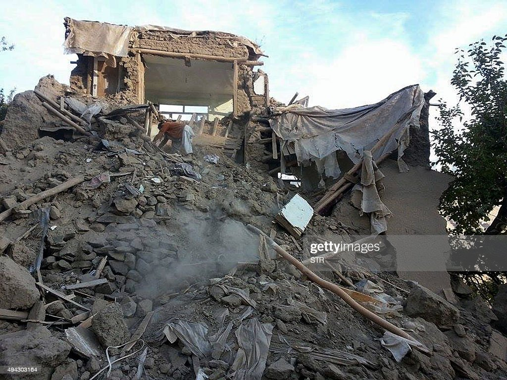 An Afghan man digs through the rubble of a damaged building after a powerful earthquake in Raman Kheel village in Panjshir valley on October 26 2015...