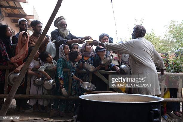 An Afghan man distributes food to poor people during the holy month of Ramadan in Ghazni on July 13 2014 Across the Muslim world the faithful fast...