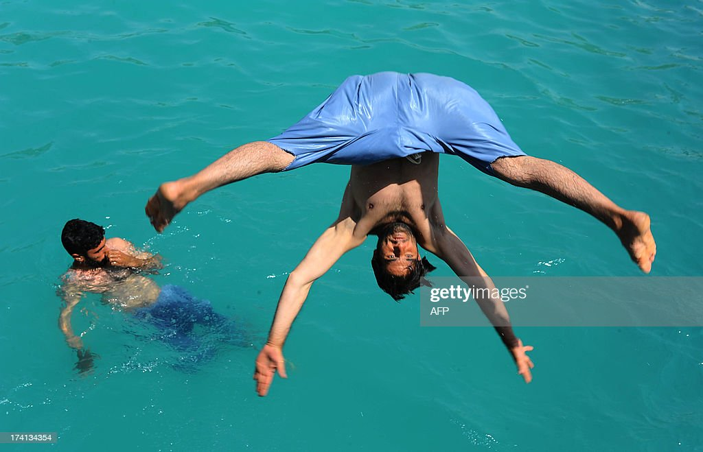 An Afghan man dives into a public swimming pool in Herat on July 20, 2013. Temperatures in Afghanistan cities are approaching the 30 degrees Celsius mark as the summer sets in in Central Asia. AFP PHOTO/ Aref KARIMI