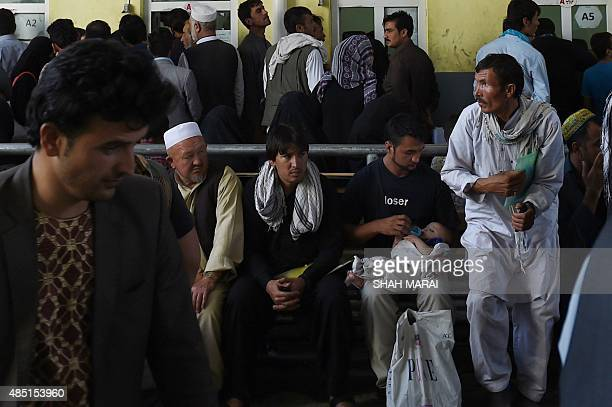 An Afghan man feeds his baby as he waits with others to apply for passports at the passport office in Kabul on August 25 2015 The toppling of the...