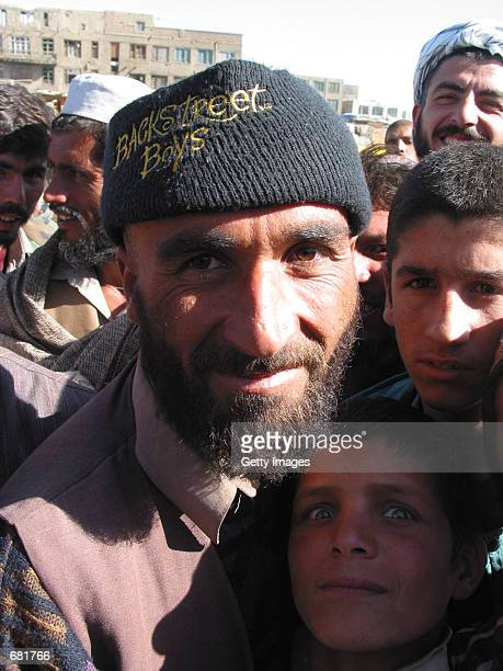 An Afghan man in a hat displaying the logo for the pop group the Backstreet Boys says he will have his beard trimmed November 14 2001 in Kabul...