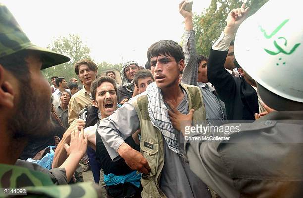 An Afghan man is held back by police during a demonstration against Pakistan July 8 2003 near the Pakistan Embassy in Kabul Afghanistan Recent...