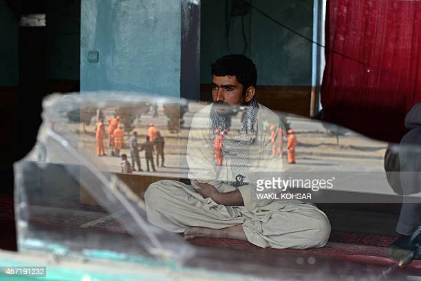 An Afghan man looks on as the scene of a blast site is reflected on a broken window following an explosion from a magnetic bomb attached to a...