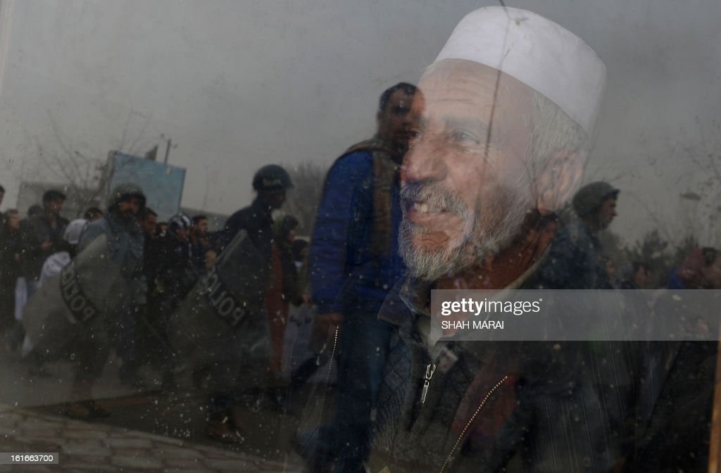 An Afghan man looks through window of his shop as women march during a protest calling for an end to violence against women in Afghanistan and around the world, in Kabul on February 14, 2013. According to a UN report, Afghanistan has made progress in protecting women against violence, but many still suffer horrific abuse 11 years after a US-led invasion brought down the Taliban regime. Afghan women still endure killings by relatives in the name of family honour, forced marriages and domestic abuses. AFP PHOTO/SHAH Marai