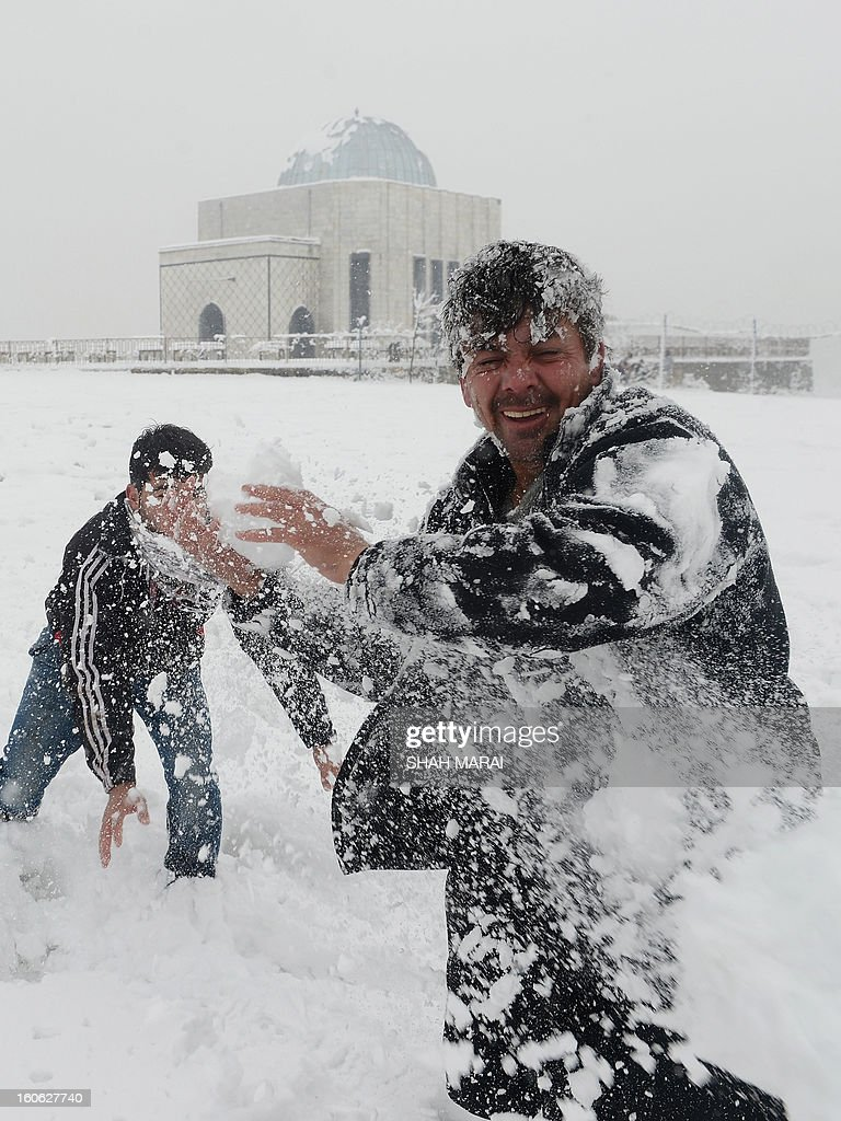 An Afghan man plays with youths in the snow in Kabul on February 4, 2013. As winter sets in across Central Asia, many Afghans struggle to provide adequate food and shelter for their families. AFP PHOTO/ SHAH Marai