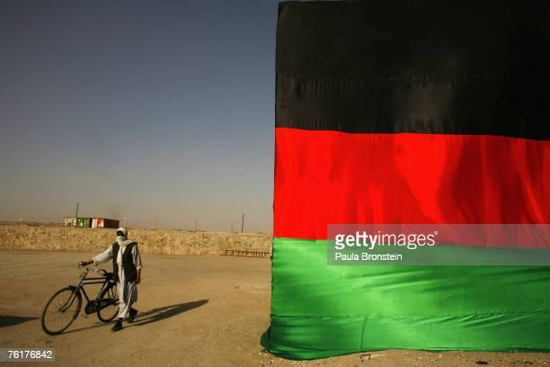 An Afghan man poses beside a large Afghanistan flag as the country celebrates Independence day on August 19 2007 in Kabul Afghanistan Afghanistan has...