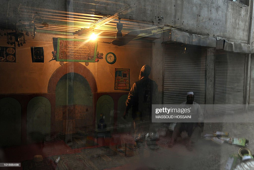 An Afghan man (C) prays at a mosque as a worker is reflected in the window in the old section of Kabul on May 2, 2010. A British soldier died in an explosion in southern Afghanistan while protecting fellow troops as they returned from a patrol, officials said May 2. The soldier, from 1st Battalion The Mercian Regiment, was serving with 40 Commando Royal Marines Battle Group and died near a patrol base in Sangin, Helmand Province. AFP PHOTO/Massoud HOSSAINI