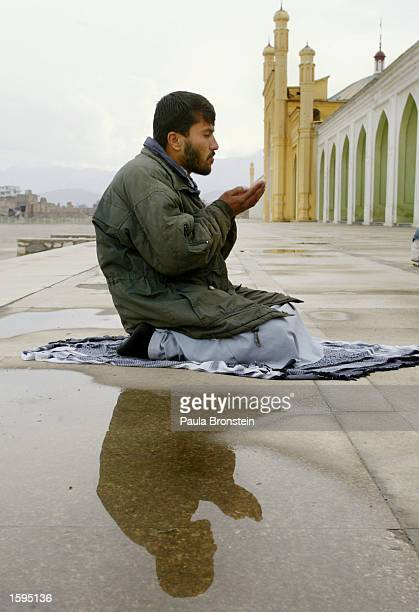 An Afghan man prays on the first day of the Muslim fasting month of Ramadan in front of Eid Gah Mosque November 5 2002 in Kabul Afghanistan