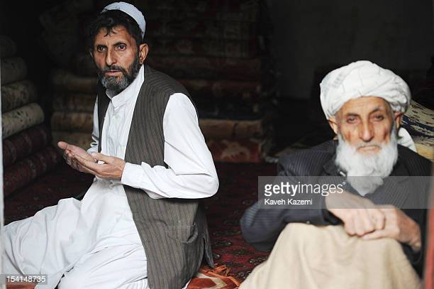 An Afghan man prays while sat in a carpet shop with his father in Chicken Street on October 17 2011 in Kabul Afghanistan Chicken Street has been a...