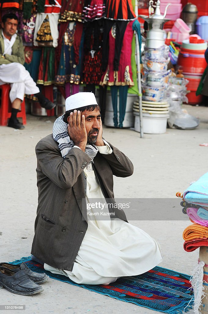An Afghan man puts his prayers while sat on the pavement in a busy market place on October 15, 2011 in Kabul, Afghanistan.