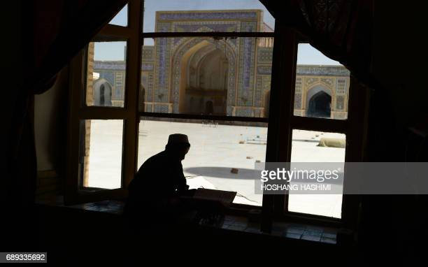 An Afghan man reads the Koran during the Islamic holy month of Ramadan at a mosque in Herat province on May 28 2017 Muslims throughout the world are...
