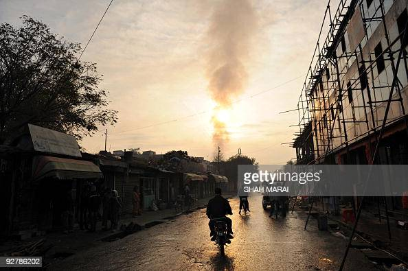 An Afghan man rides his motorcycle as the smouldering Bekhtar guesthouse is seen in the background during sunrise in Kabul on October 28 where UN...