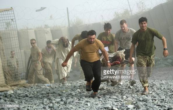 An Afghan man runs after his son as is carried to the Medevac of 159th Brigade Task Force Thunder to be airlifted to Kandahar Hospital Hero on August...