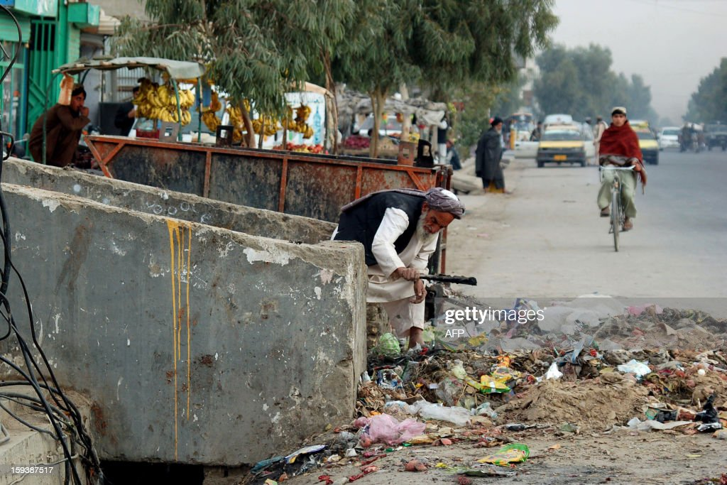 An Afghan man searches a garbage dump for useful items in Kandahar on January 12, 2013. AFP PHOTO/Mamoon Durrani