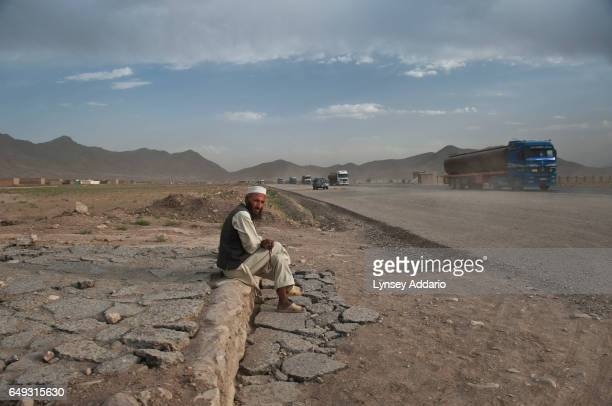 An Afghan man sits along the side of the road near the mostly abandoned land allocation settlement of AliceGhan about 30 miles outside of Kabul...