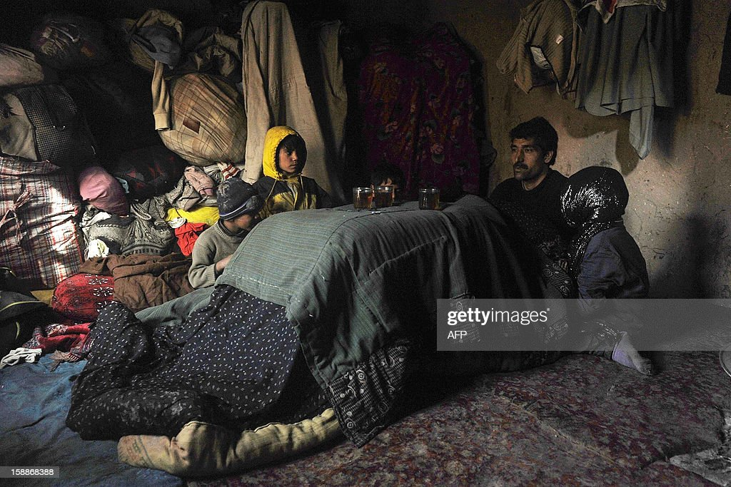 An Afghan man sits with his children amid thick blankets at a refugee camp in Herat on January 2, 2013. Hundreds of families living in makeshift shelters around the Afghan capital Kabul collected blankets, charcoal and other supplies on January 2 as authorities struggle to avoid last year's deadly winter toll. With temperatures dropping to -10 Celsius (14 Fahrenheit) at night in the city, the 35,000 refugees who live in the snow-covered camps face a battle to survive dire conditions protected only by plastic sheeting. AFP PHOTO/ Aref Karimi