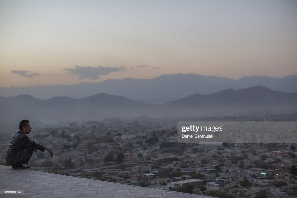 An Afghan man smokes a cigarette as sits in a park overlooking Kabul on November 5, 2012 in Kabul, Afghanistan.