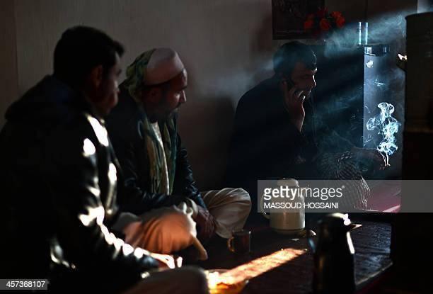 An Afghan man talks on the phone as he smokes in a tea house in Mahmud Raqi capital of Kapisa province on December 17 2013 Even with sustained growth...