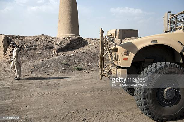 An Afghan man walks past a mineresistant armored vehicle carrying members of the US Army near Kandahar Airfield on June 3 2014 Members of the 1st...