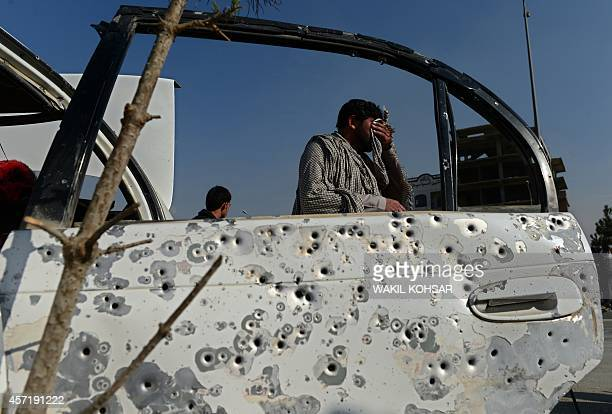 An Afghan man walks past a shrapnelriddled car door at the scene following an explosion from a magnetic bomb attached to a civilian car in Kabul on...