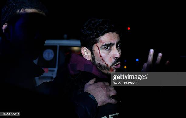 TOPSHOT An Afghan man with blood on his face reacts after a suicide car bomb attack which targeted a compound for foreign contractors in Kabul on...
