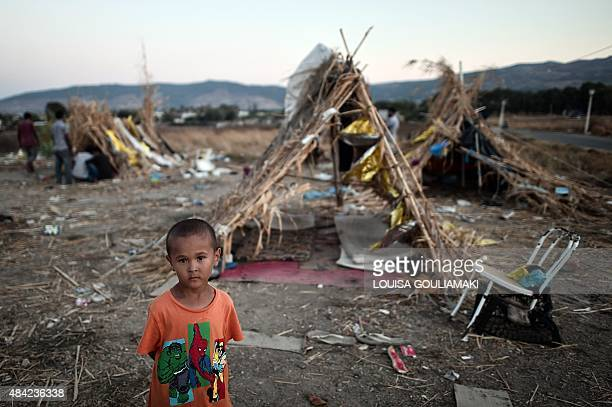 An Afghan migrant child stands in front of makeshift shelters on August 16 outside the abandoned Captain Elias hotel on the Greek Aegean island of...