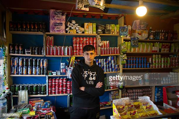 An Afghan migrant poses for a photograph inside a shop in the camp known as 'The Jungle' on January 5 2016 in Calais France Thousands of migrants...