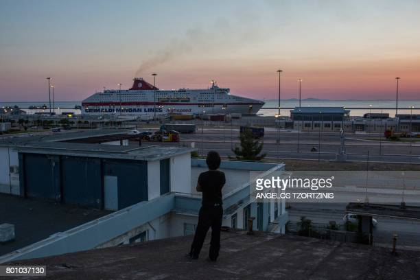 TOPSHOT An Afghan migrant stands on roof top at an abandoned factory which has been his temporary home in Patras southwestern Greece on June 20 2017...