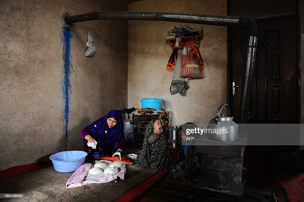An Afghan mother makes bread for her children in Herat on January 27, 2014. Some nine million Afghans or 36 percent of the population are living in 'absolute poverty' while another 37 percent live barely above the poverty line, according to a UN report. AFP PHOTO/Aref Karimi