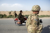 An Afghan motorcyclist rides past US soldiers on patrol near Kandahar Airfield on June 3 2014 Members of the 1st Battalion 12th Regiment 4th Brigade...