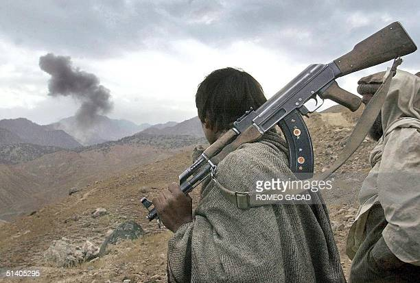 An Afghan mujahedin fighter watches mushroom clouds rise in Tora Bora as US warplanes bomb positions held by Osama bin Laden's alQaeda fighters 13...