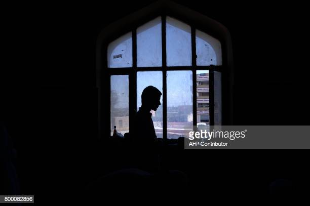 TOPSHOT An Afghan Muslim offers his prayers on the last Friday of the holy month of Ramadan ahead of the Muslim festival of Eid alFitr at a mosque in...
