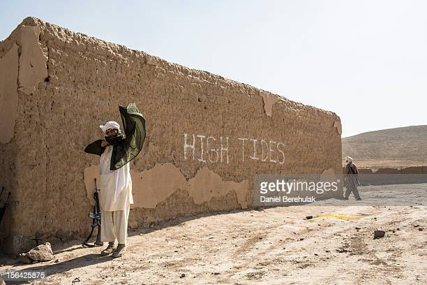An Afghan National Army cadet dressed as Taliban adjusts himself following a Taliban capture military exercise overseen by French and Canadian...