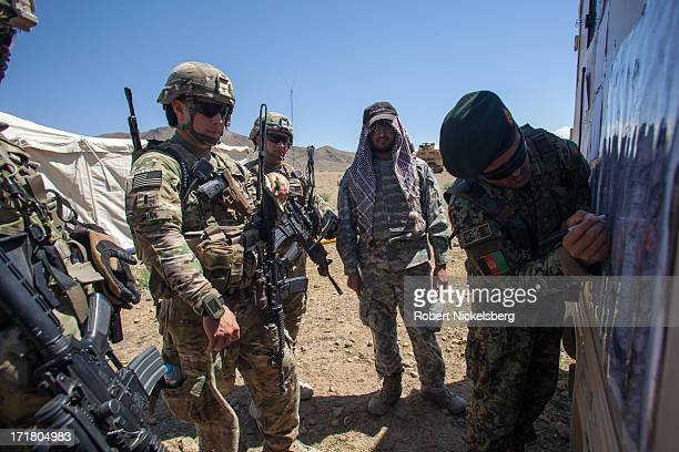 An Afghan National Army commanding officer right explains a map position to his US Army counterparts from the 4th Brigade 3rd Infantry Division May 6...