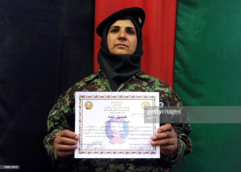 An Afghan National Army (ANA) female officer holds up her graduation certificate during a ceremony at the ANA training centre in Herat on January 22, 2013. International troops in Afghanistan and all NATO-led combat forces are due to leave by the end of 2014, when Kabul will assume responsibility for the country's security. Some 300,000 Afghan Army and Police personnel have been trained so far. AFP PHOTO/ Aref Karimi