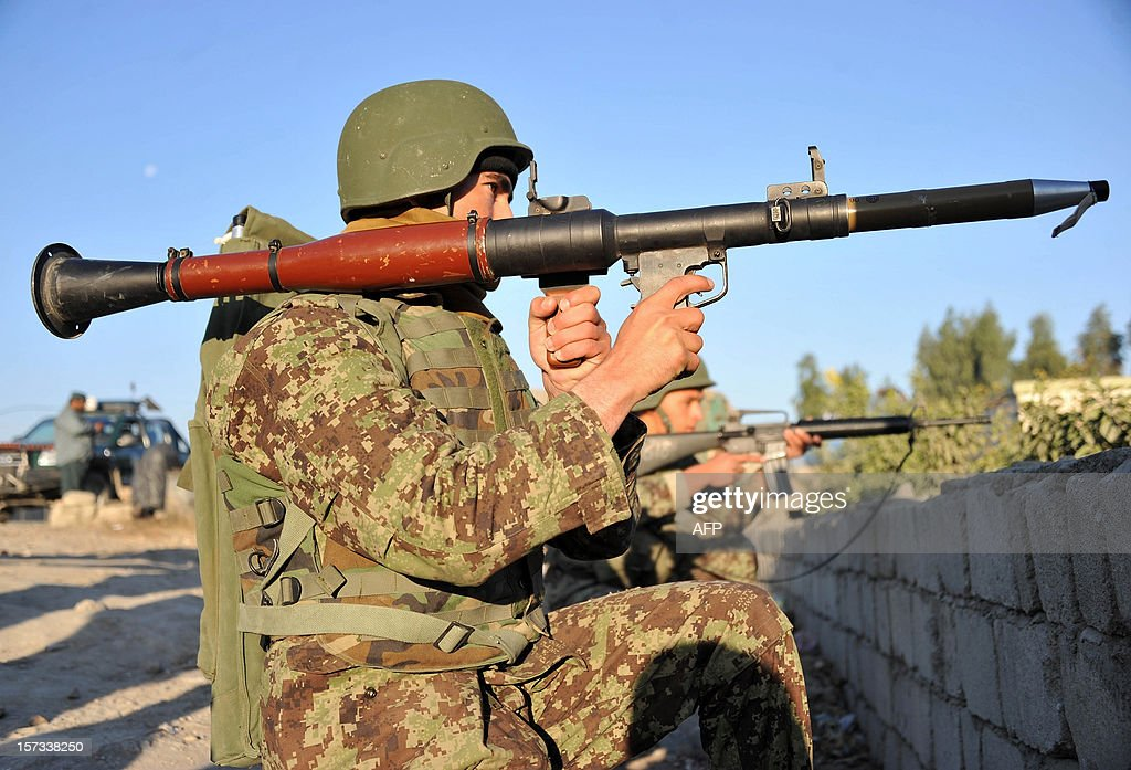 An Afghan National Army (ANA) soldier holds a rocket-propelled grenade (RPG) launcher as he keeps watch near the scene of a suicide attack in Jalalabad on December 2, 2012. Taliban insurgents launched a major suicide attack against a NATO base at an Afghan city airport, killing three Afghan guards and wounding several foreign troops, officials said. NATO helicopters fired on the insurgents as they followed up a car bombing at the perimeter gate of the Jalalabad airport with rocket-propelled grenades, mortars and small arms fire. AFP PHOTO/ Noorullah Shirzada