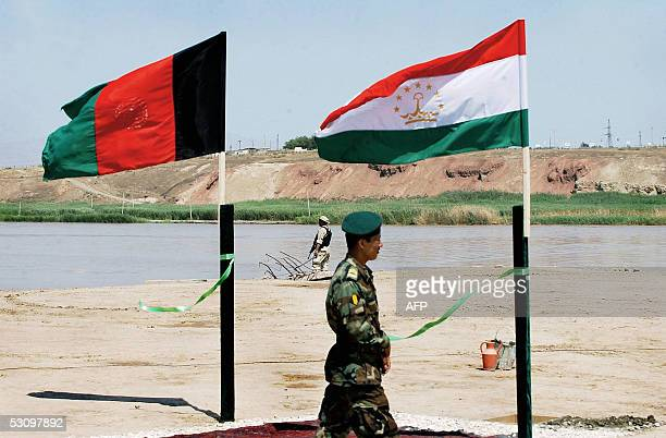 An Afghan National Army soldier passes the flags of Afghanistan and Tajikistan during a ceremony for a new USfunded bridge linking Afghanistan and...