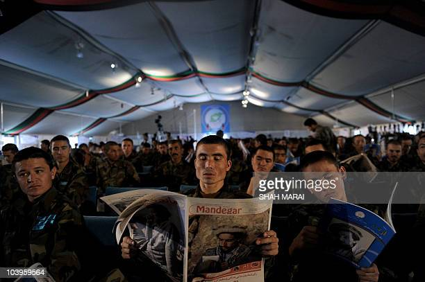 An Afghan National Army soldier reads a magazine with a portrait of late resistance leader Ahmad Shah Masood during a ceremony to mark the ninth...