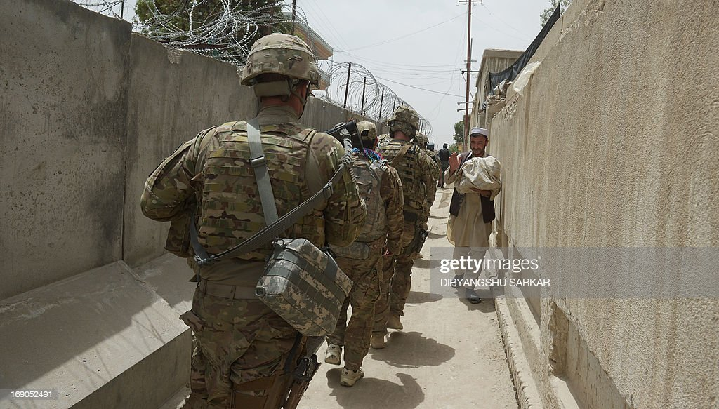 An Afghan national carrying traditional bread walks past soldiers of the 10th Mountain Division US Army at the provincial head Intelligence Office of the Afghan National Police in Ghazni city on May 19, 2013. Afghan security forces are increasingly on the front line against the insurgents, and suffering heavier casualties, as NATO combat troops prepare to withdraw by the end of next year. AFP PHOTO/ Dibyangshu SARKAR