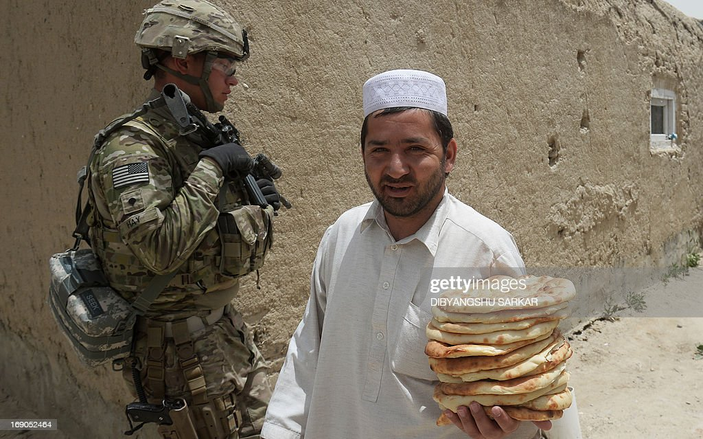 An Afghan national carrying traditional bread walks past Specialist Hay of the 10th Mountain Division US Army at the provincial head Intelligence Office of the Afghan National Police in Ghazni city on May 19, 2013. Afghan security forces are increasingly on the front line against the insurgents, and suffering heavier casualties, as NATO combat troops prepare to withdraw by the end of next year. AFP PHOTO/ Dibyangshu SARKAR