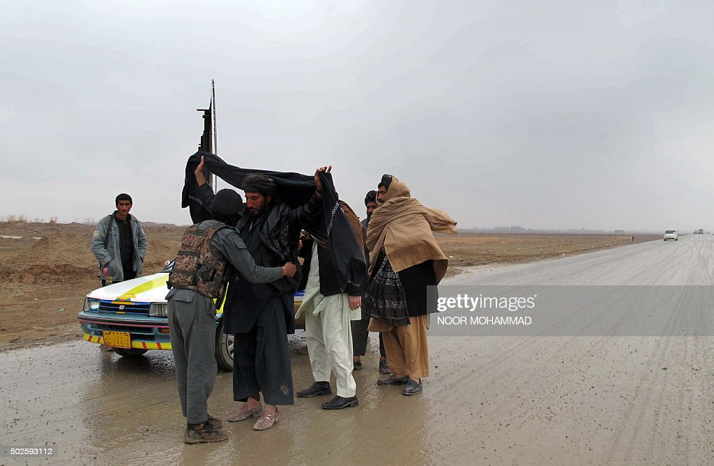 An Afghan National policeman searches a passenger at a checkpoint in the Sangin district of Helmand province on December 27 2015 Afghan forces are...