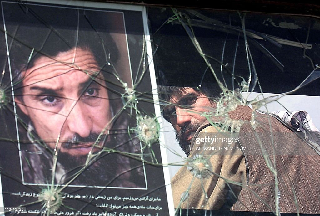 An Afghan Northern Alliance soldier looks through the bullet marked window of his car with the portrait of Ahmad Shah Masood on the front line...