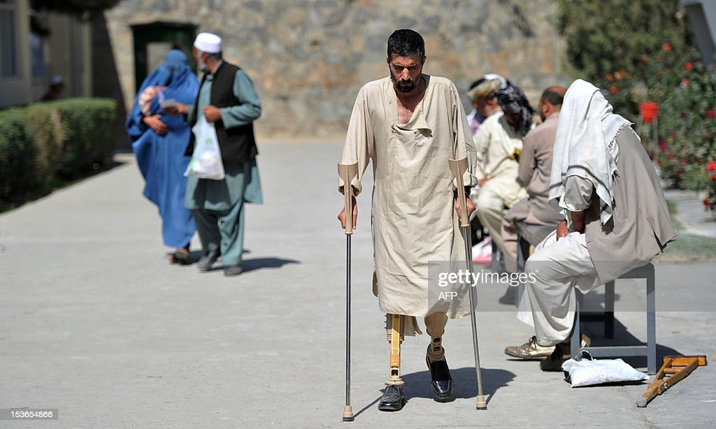 An Afghan patient who has lost his legs in a landmine in Kandahar walks with the aid of crutches at The International Red Cross Centre (ICRC) in Kabul on October 8, 2012. The Afghan government could implode after NATO troops pull out in 2014, particularly if presidential elections are fraudulent, a report by the International Crisis Group said. AFP PHOTO/JAWAD JALALI