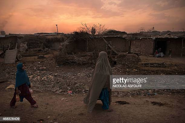 An Afghan pedestrian and a child whose family fled their home country to Pakistan walk through a slum on the outskirts of Islamabad on February 10...