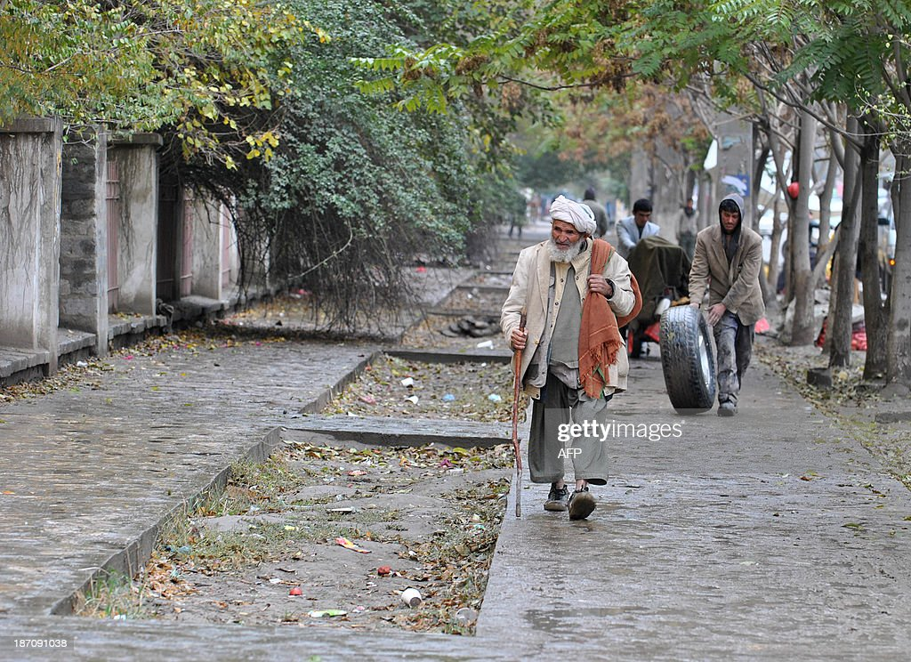 An Afghan pedestrian walks along a street on a rainy day in Kabul on November 6, 2013. Despite massive injections of foreign aid since the fall of the Taliban in 2001, Afghanistan remains desperately poor as it attempts to recover from decades of conflict. AFP PHOTO / Farshad USYAN