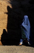 An Afghan pedestrian walks along a street on the outskirts of Herat on April 14 2014 Afghanistan is currently heavily dependent on foreign donors but...