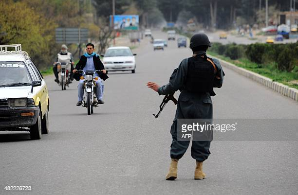 An Afghan policeman asks commuters to pull over to be searched at the southern entrance t the northwestern city of Herat on April 3 2014 Afghans will...