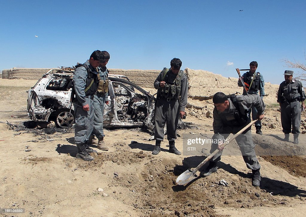 An Afghan policeman digs alongside a destroyed car after a NATO helicopter strike on the outskirts of Ghazni on March 30, 2013. A NATO helicopter strike killed two children in south Afghanistan on Saturday, officials said, in the latest civilian casualities to beset the coalition's war against Taliban militants.