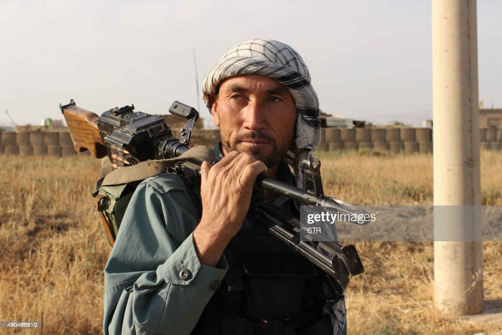 An Afghan policeman holds a gun on his sholder a day after Taliban insurgents overran the strategic northern city of Kunduz on September 29 2015...